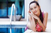 stock photo of woman dragon  - beautiful slim woman by the swimming pool with a dragon fruit - JPG