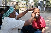 KOLKATA, INDIA - FEBRUARY 09, 2014: Street barber shaving a man using an open razor blade on a street in Kolkata, West Bengal, India