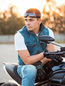 Biker Man Sitting On His Motorcycle Outdoors