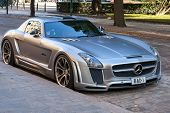 Silver metallic Mercedes-Benz SLS roadster tuned by FAB Design stands parked on a street side of Hel