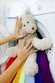 Woman Loading Fluffy Toy In The Washing Machine