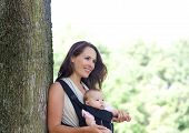 Mother Smiling With Infant In Baby Carrier