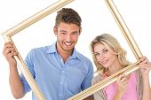 Portrait of attractive young couple smiling at camera through picture frame over white background