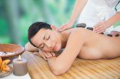 Beautiful brunette enjoying a hot stone massage at a luxury spa