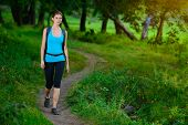 Young Beautiful Woman Hiking on the Trail in the Green Summer Forest