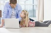 Father and daughter using laptop on floor in living room