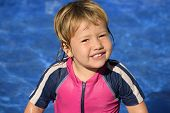 Happy kid with sun protection swimwear smiling in the swimming pool