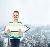 advertising, direction and childhood concept - smiling little boy with white blank arrow pointing up