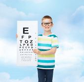 vision, ophthalmology, childhood and people concept - smiling little boy in eyeglasses with with eye