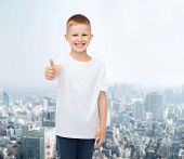 advertising, people and childhood concept - smiling little boy in white blank t-shirt showing thumbs