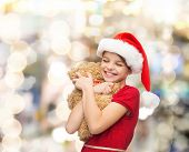 holidays, presents, christmas, childhood and people concept - smiling girl in santa helper hat with teddy bear over lights background