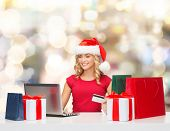 christmas, holidays, technology and shopping concept - smiling woman in santa helper hat with gifts,