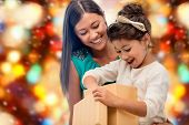 christmas, holidays, celebration, family and people concept - happy mother and child girl with gift