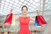 shopping, sale, christmas and holiday concept - laughing elegant woman in red dress with shopping ba