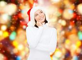 christmas, holidays, winter, happiness and people concept - thinking and smiling woman in santa help