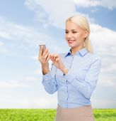 business, technology, internet and education concept - smiling young businesswoman with smartphone