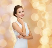 holidays, celebration, wedding and people concept - smiling woman in white dress wearing diamond rin