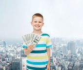 financial, planning, childhood and concept - smiling boy holding dollar cash money in his hand over