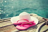 beach, summer, vacations and accessories concept - close up of hat and slippers at seaside