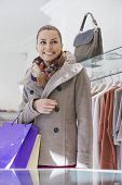 Happy young woman with shopping bags in store