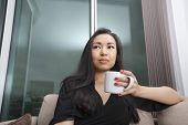 Thoughtful young woman having coffee in living room