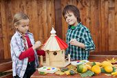 Kids painting a bird house in autumn