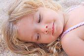 Little Girl Lying On The Sand