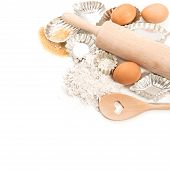 Baking Ingredients Eggs, Flour, Sugar And Cookie Cutters Over White