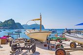 stock photo of trailer park  - The small fishing boat stands on the boat trailer on the embankment of the small harbor of Petrovac Montenegro.