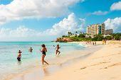 People Relaxing On Sunset Beach Of Sint Maarten, Caribbean Island