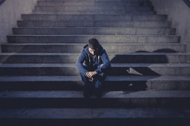 stock photo of underworld  - Young desperate man in casual clothes abandoned lost in depression sitting on ground street concrete stairs alone suffering emotional pain sadness looking sick in grunge lighting - JPG