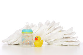 foto of nipples  - New born child stack of diapers nipple soother baby feeding milk bottle with water and yellow duck on a white background - JPG