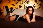 foto of laying-in-bed  - Sexy woman in stockings laying on bed at night