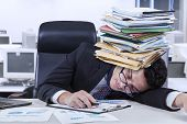 foto of boredom  - Caucasian businessperson sleeping in the office with documents on his head shot in the office - JPG