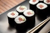 stock photo of chopsticks  - maki sushi on black plate with chopsticks - JPG