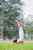 image of locust  - Beautiful woman practicing yoga in the park - JPG