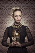 stock photo of gothic female  - pretty blonde female posing in carnival shot with antique gothic lace dress baroque jewellery and precious mask in the hands - JPG