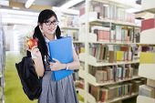 image of indian apple  - Young attractive female student standing in the library while holding a red apple and folder - JPG
