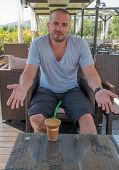 picture of frappe  - Greek man relaxing and drinking a Frappe - JPG