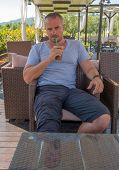 stock photo of frappe  - Greek man relaxing and drinking a Frappe - JPG