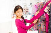 Asian girl stands and holds the sweater's arm
