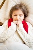 picture of ling  - Closeup portrait of little girl in sweater ling in bed under blanket - JPG