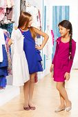 Two girls shop and one asks other about the dress