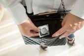Young Woman Putting Condom In Handbag