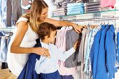 Mother with child searches clothes while  shopping