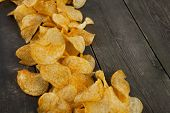 stock photo of potato chips  - many potato chips with text space on a wooden background - JPG