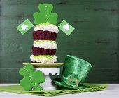 stock photo of leprechaun hat  - Happy St Patricks Day triple layer cupcake with shamrock decorations and leprechaun hat against a vintage style green wood background - JPG