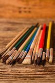 Color Paintbrushes On Vertical Photo Placed On Wooden Board