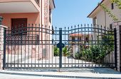 stock photo of gate  - Steel security gates leading to a residential area - JPG