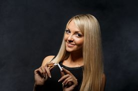 stock photo of tobacco smoke  - Happy young confident woman quitting smoking stands with the broken cigarette on a dark background with smoke - JPG